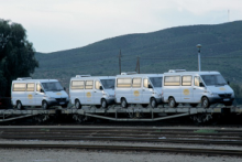 Air-conditioned touring vehicles transported together on the train.